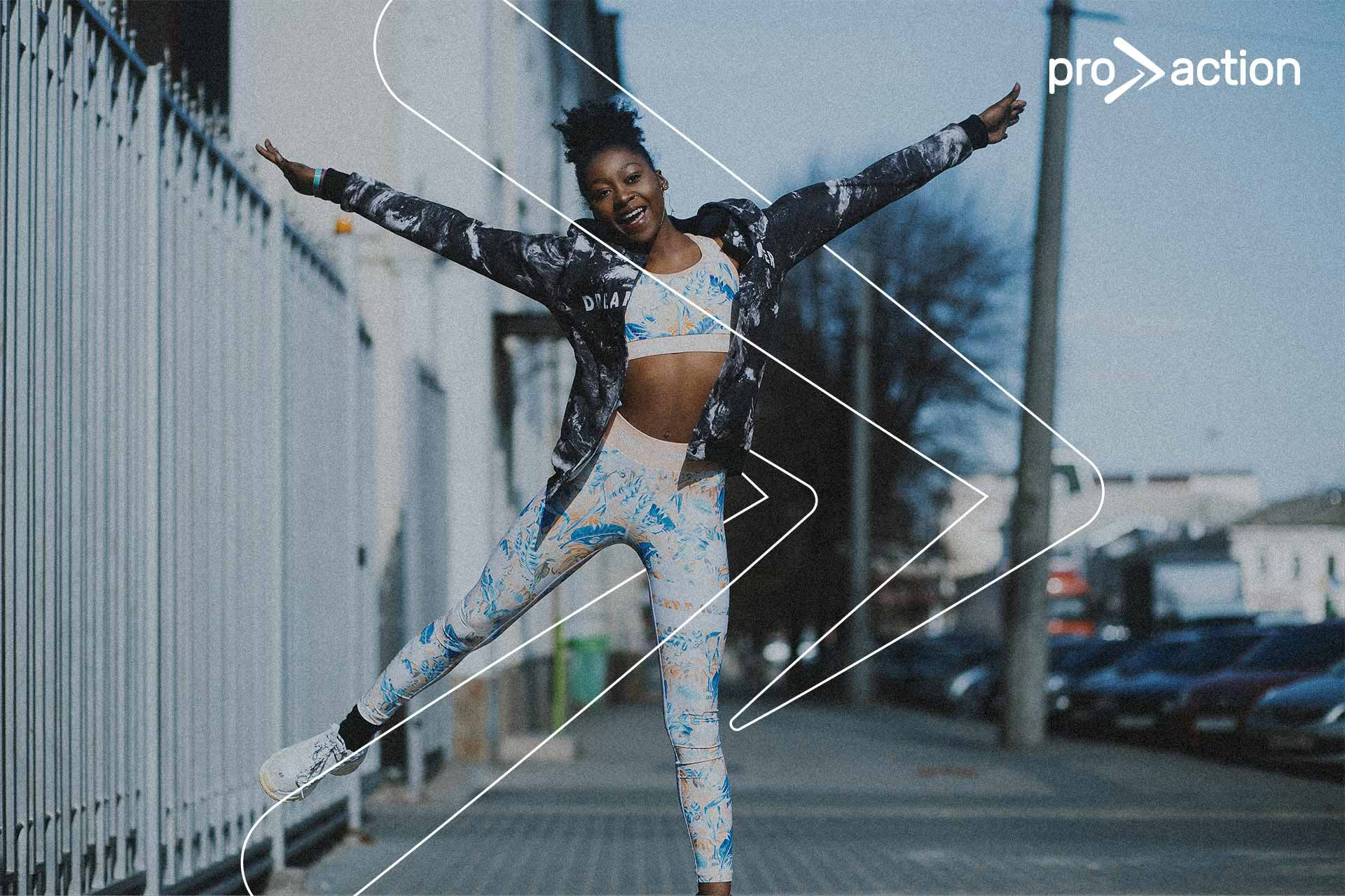Carefree black woman wearing Pro Action yoga pants and gym clothes dancing in street